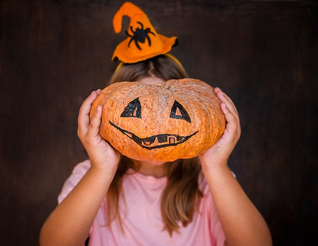 Gelukkig kindmeisje dat op heksenhoed halloween pumpink in plaats van gezicht houdt