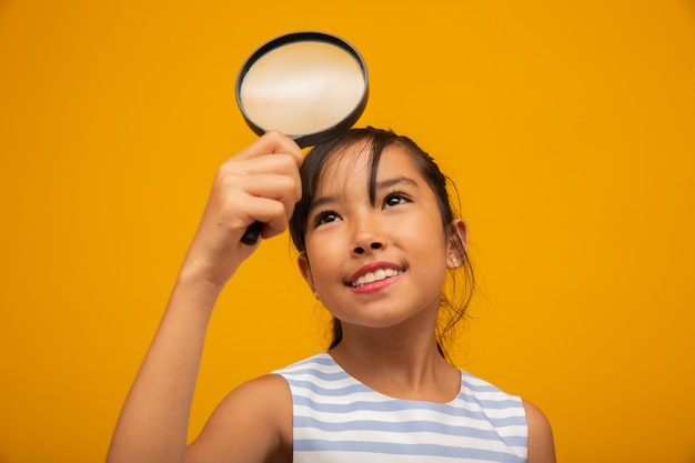 Gelukkig klein aziatisch kind met vergrootglas
