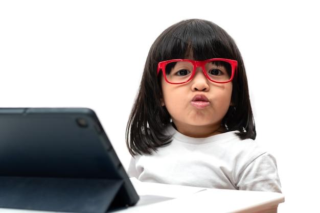 Gelukkig klein aziatisch kleutermeisje dat een rode bril draagt en een tablet-pc en een grappig gezicht gebruikt