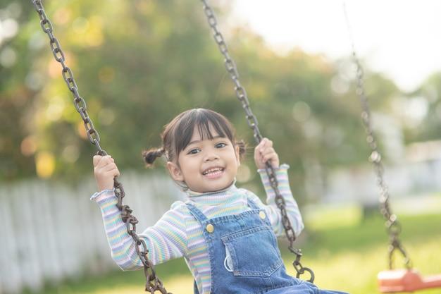 Gelukkig klein aziatisch meisje dat buiten in het park schommelt