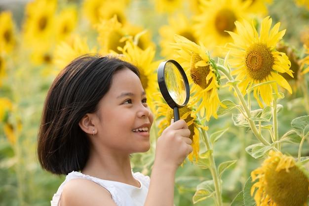 Gelukkig klein aziatisch meisje met plezier tussen bloeiende zonnebloemen onder de zachte stralen van de zon.