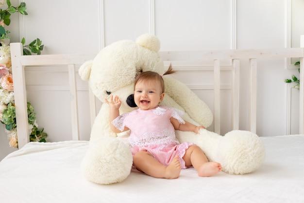 Gelukkig klein babymeisje zes maanden oud zittend op een wit bed in roze kleren, met een grote teddybeer en lachend