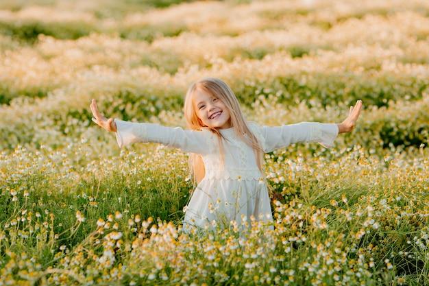 Gelukkig klein blond meisje in witte katoenen jurk hief haar handen op in een veld van madeliefjes