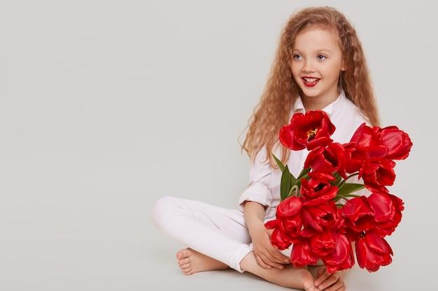 Gelukkig klein blond meisje wegkijken met brede glimlach en positieve gezichtsuitdrukking, zittend op de vloer, boeket van rode tulpen te houden