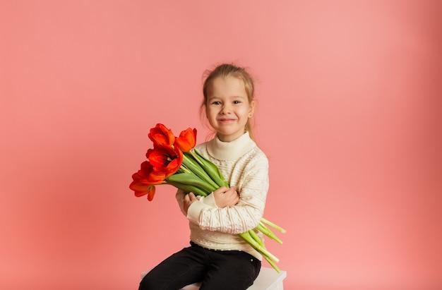 Gelukkig klein blondemeisje die en rode tulpen op roze muur zitten houden