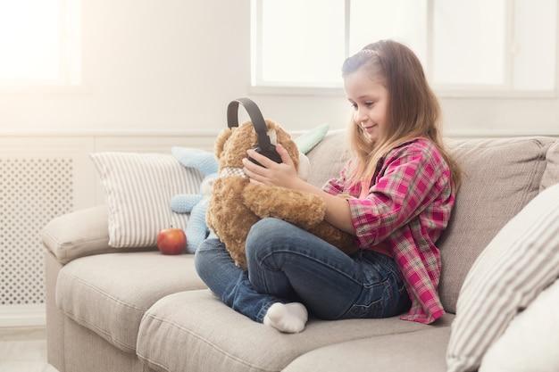 Gelukkig klein casual meisje dat haar teddybeer in een koptelefoon houdt. mooi kind thuis, zittend op de bank met favoriet speelgoed en naar muziek luisteren, ruimte kopiëren