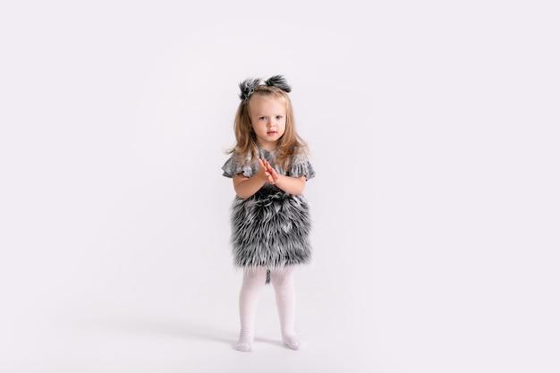 Gelukkig klein grappig emotioneel kindmeisje in leuk kerstwolfkostuum