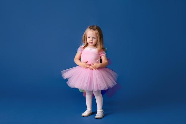 Gelukkig klein grappig emotioneel kindmeisje in leuk roze ponykostuum op blauw gekleurde achtergrond.