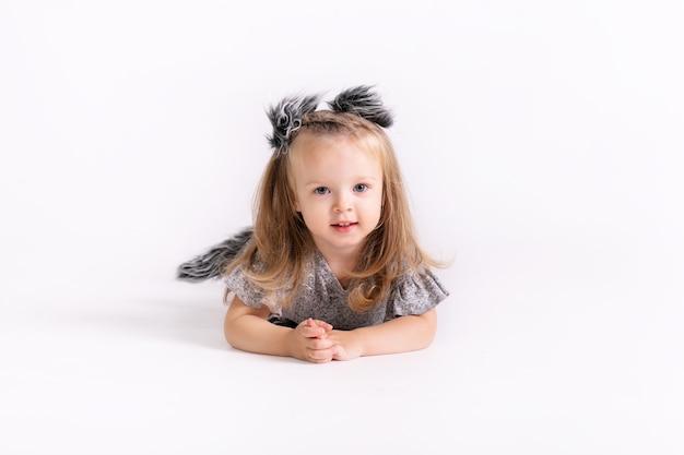 Gelukkig klein grappig emotioneel kindmeisje in leuk wolfskostuum op wit gekleurde achtergrond.