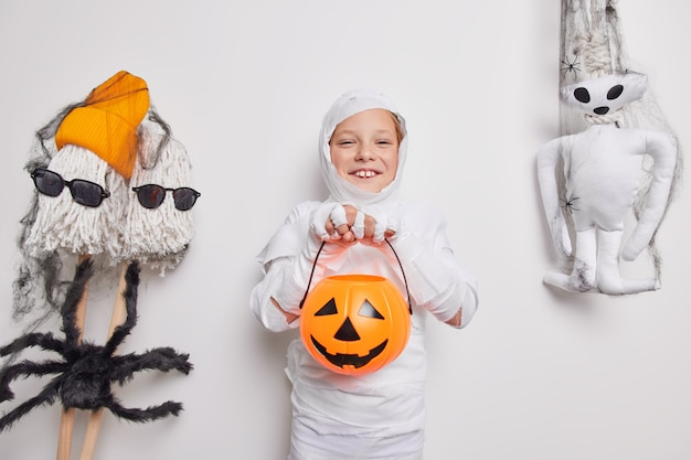 Gelukkig klein halloween-kind speelt trick or treat jack o lantern pompoen gewikkeld in witte stof omgeven door vakantieattributen geïsoleerd op wit