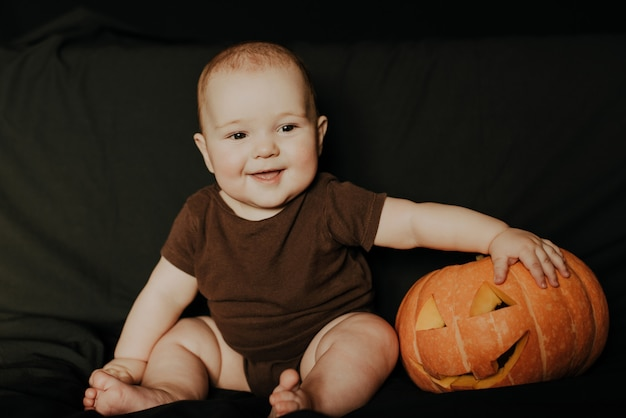 Gelukkig klein jongensjong geitje dat met halloween-pompoen lacht