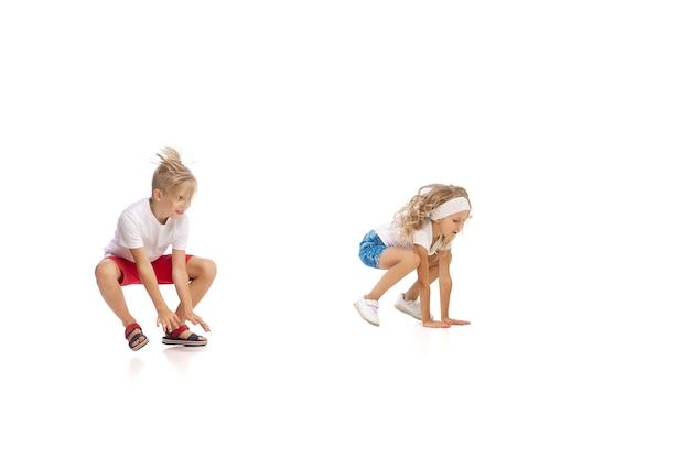 Gelukkig klein kaukasisch meisje en jongen springen en rennen geïsoleerd op een witte achtergrond