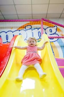Gelukkig klein kind, babymeisje 1-2 jaar, kinderen rijden omhoog, omlaag op glijbaan in gamecentrum, pretpark van de kinderkamer voor verjaardag. binnenspeeltuin.