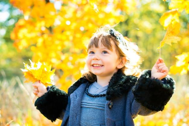 Gelukkig klein kind, babymeisje lachen en spelen in de herfst op de natuurwandeling buiten.