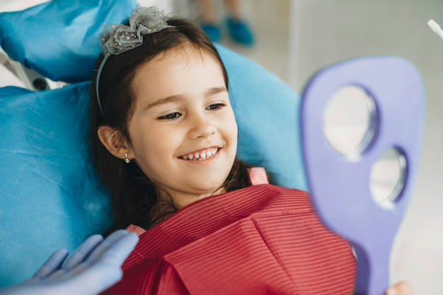Gelukkig klein kind in de spiegel kijken na onderzoek van de tanden in een pediatrische stomatologie.