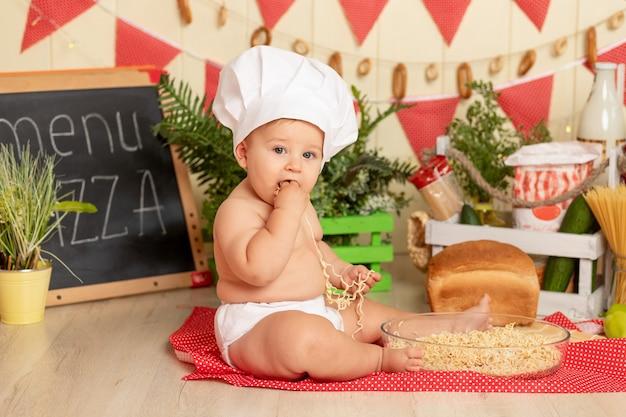 Gelukkig klein kind koken in een hoed, zittend in de keuken tussen de producten en spaghetti eten