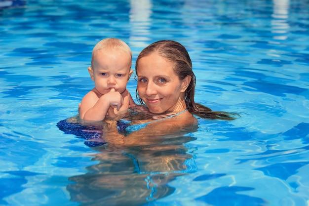 Gelukkig klein kind leren zwemmen met jonge moeder in zwembad.