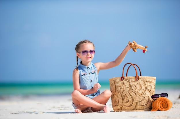 Gelukkig klein kind met speelgoed vliegtuig in handen op witte zandstrand