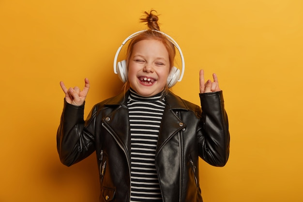 Gelukkig klein kind rocker maakt hoorn handteken, rock n roll gebaar, geniet van favoriete muziek of melodie in draadloze hoofdtelefoons, draagt leren jas, giechelt gelukkig, geïsoleerd op gele muur