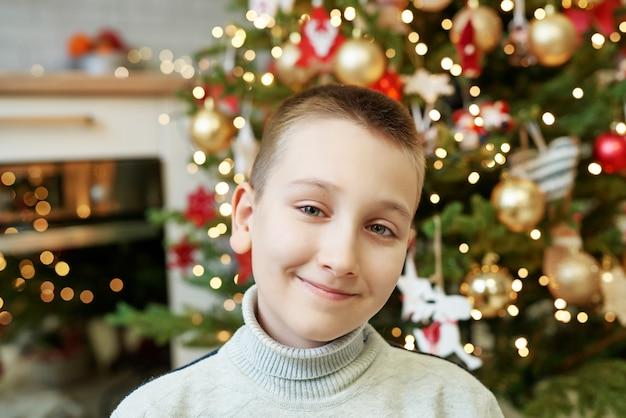 Gelukkig klein kind zit in de buurt van de kerstboom