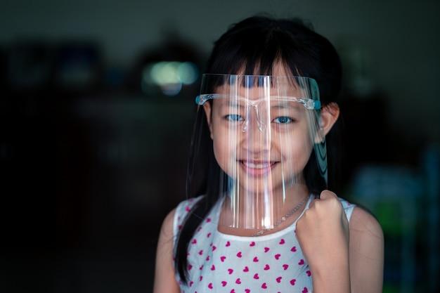 Gelukkig klein kindmeisje met een plastic gelaatsscherm voor een virusbeschermingsmasker op zijn gezicht