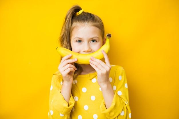 Gelukkig klein kindmeisje met gele banaan zoals glimlach op gele achtergrond