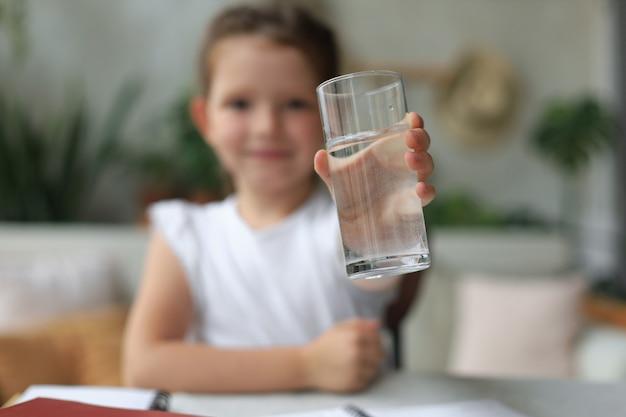 Gelukkig klein meisje biedt kristalhelder mineraalwater uit glas, klein kind raadt dagelijkse dosis schone aqua aan.