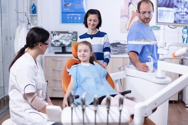 Gelukkig klein meisje bij pediatrische tandarts die tandslab draagt tijdens stomatologisch onderzoek. kind met haar moeder tijdens tandencontrole met stomatolog zittend op een stoel.