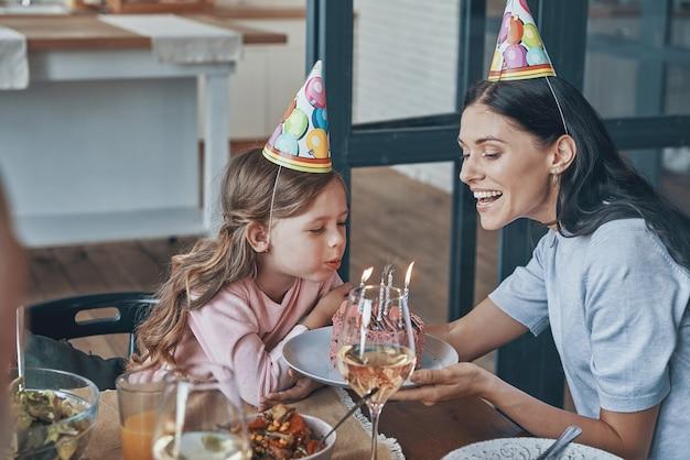 Gelukkig klein meisje blaast kaarsen op verjaardagstaart tijdens het diner met familie
