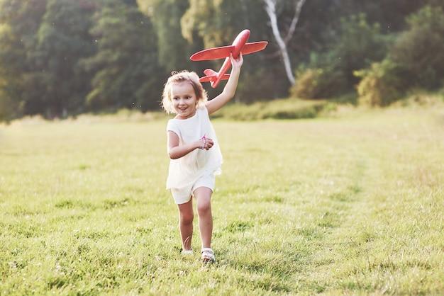 Gelukkig klein meisje dat op het veld loopt met een rood speelgoedvliegtuig in hun handen