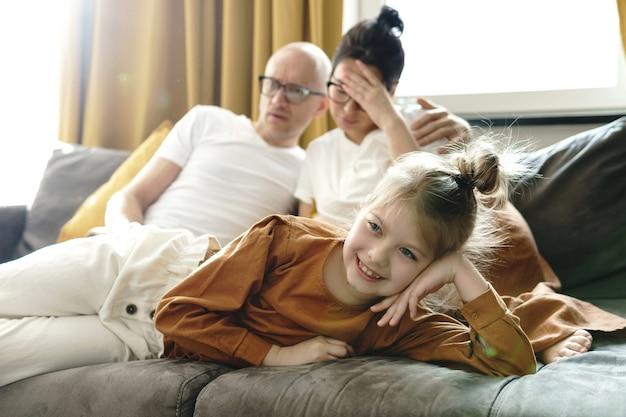 Gelukkig klein meisje dat thuis tekenfilms kijkt met haar vermoeide ouders
