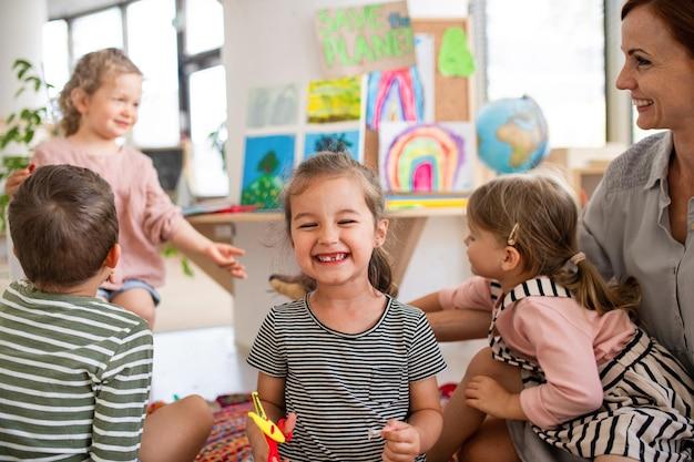 Gelukkig klein meisje dat verloren melktanden binnenshuis in de klas laat zien, kijkend naar de camera.