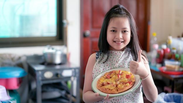 Gelukkig klein meisje dat zelfgemaakte pizza bereidt in de huiskeuken