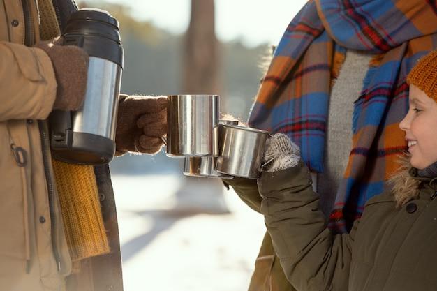 Gelukkig klein meisje en haar ouders in warme winterkleding rammelend met metalen mokken met hete thee terwijl ze buiten warm worden op een ijzige winterdag
