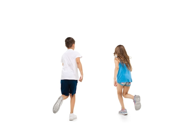 Gelukkig klein meisje en jongen die op witte muur lopen