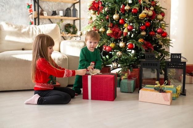 Gelukkig klein meisje en jongen met geschenkdoos door kerstboom