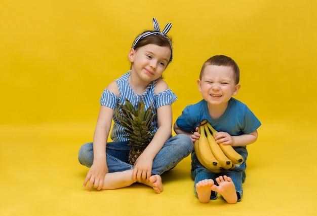 Gelukkig klein meisje en jongen zitten en houden fruit op een gele muur met ruimte voor tekst
