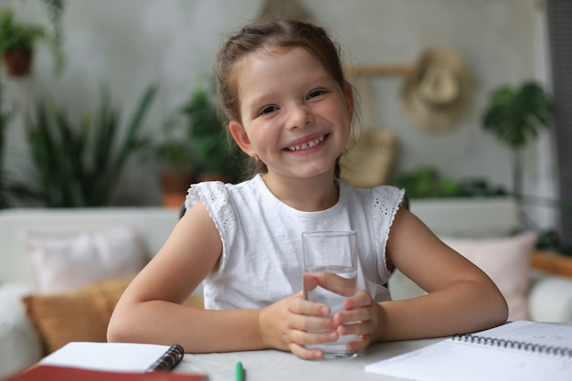Gelukkig klein meisje houdt kristalhelder mineraalwater in glas, klein kind raadt dagelijkse dosis schone aqua aan.