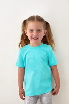 Gelukkig klein meisje in blauw shirt dat in de studio staat