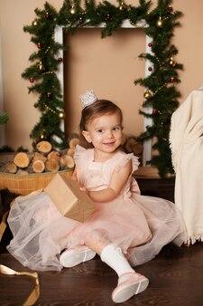 Gelukkig klein meisje in een elegante prinsessenjurk naast een kerstboom opent geschenken