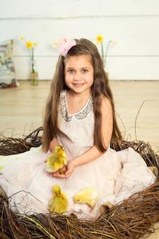 Gelukkig klein meisje in een jurk zit in een nest en houdt schattige pluizige pasen eendjes op haar handen.