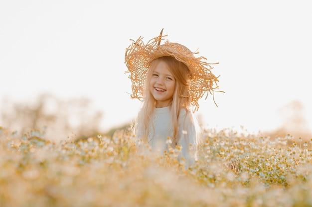 Gelukkig klein meisje in een katoenen jurk en strooien hoed loopt in een chamomo-veld in de zomer bij zonsondergang