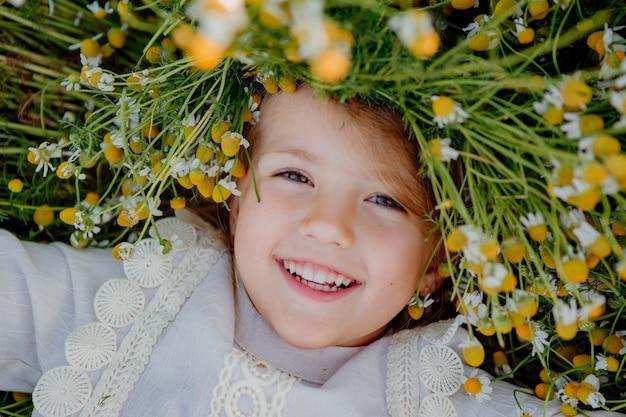 Gelukkig klein meisje in een katoenen jurk ligt in een veld met madeliefjes in de zomer bij zonsondergang. lacht, uitzicht van bovenaf