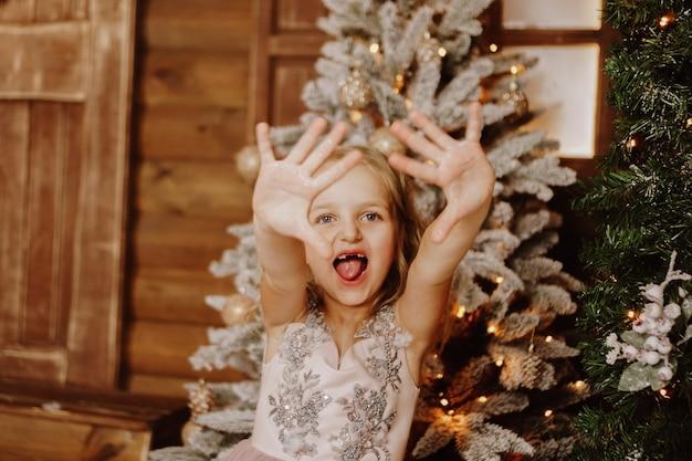 Gelukkig klein meisje in een roze jurk grimassen op de achtergrond van de kerstboom