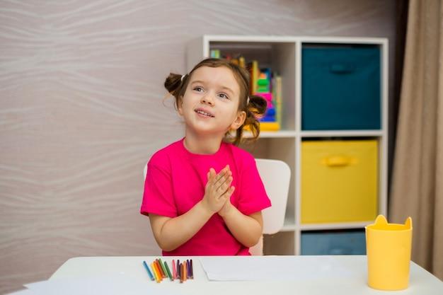 Gelukkig klein meisje in een roze t-shirt zit aan een tafel met papier en kleurpotloden