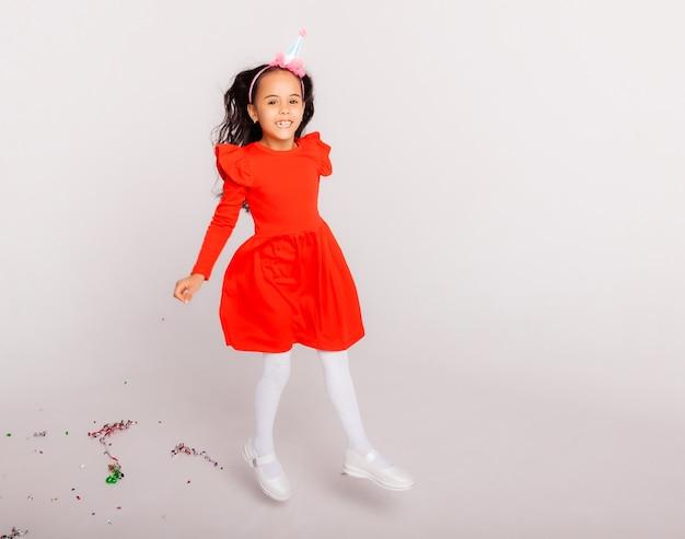Gelukkig klein meisje in een verjaardagspet houdt een grote rode geschenkdoos vast. vakantieconcept, plaats voor tekst