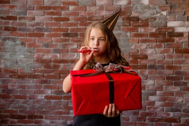Gelukkig klein meisje in een verjaardagspet houdt een grote rode geschenkdoos.