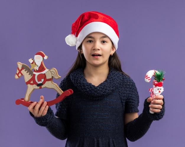 Gelukkig klein meisje in gebreide jurk met kerstmuts bedrijf kerst speelgoed kijken camera glimlachend vrolijk staande over paarse achtergrond