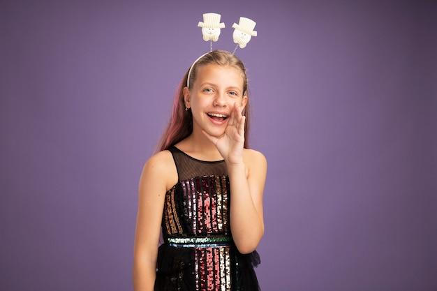 Gelukkig klein meisje in glitter feestjurk en grappige hoofdband die belt of schreeuwt met armen in de buurt van mond over paarse achtergrond