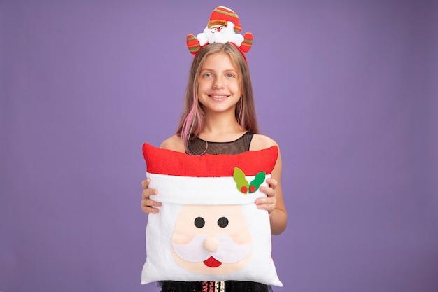 Gelukkig klein meisje in glitter feestjurk en hoofdband met santa met grappig kussen kijkend naar camera met glimlach op gezicht staande over paarse achtergrond